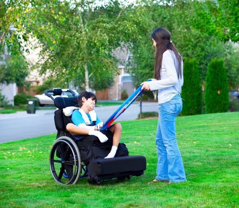 Más vieja hermana Biracial que juega al aire libre con el pequeño brot discapacitado imagen de archivo