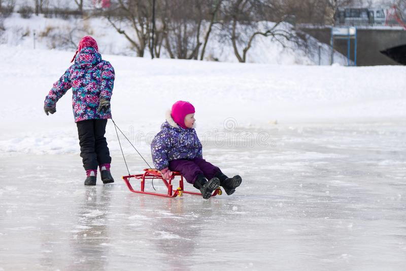 Más vieja hermana feliz que tira de su hermana joven en un trineo en el hielo en parque nevoso del invierno fotos de archivo libres de regalías