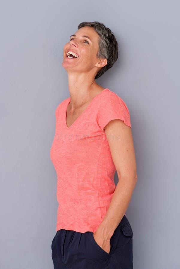 Más vieja mujer atractiva que ríe y que mira para arriba fotografía de archivo
