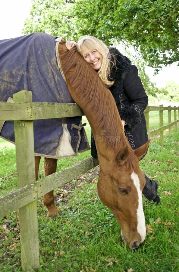 Más vieja mujer hermosa con su caballo. fotos de archivo