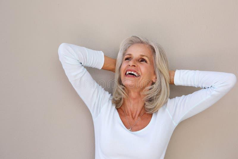 Más vieja mujer hermosa que se inclina con las manos detrás de la cabeza imagenes de archivo