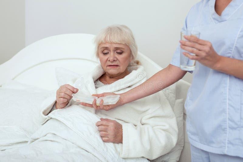 Más vieja mujer infeliz que consigue píldoras fotos de archivo libres de regalías