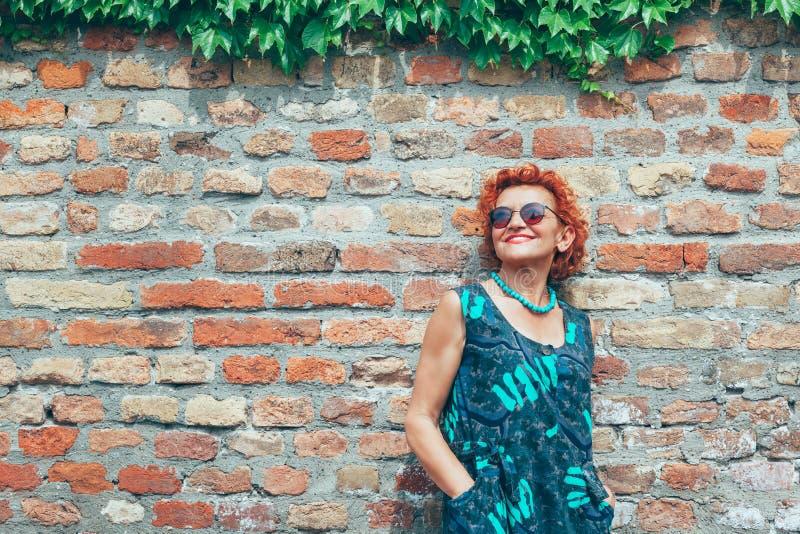 Más vieja mujer retra hermosa delante de la pared de ladrillo imagen de archivo libre de regalías