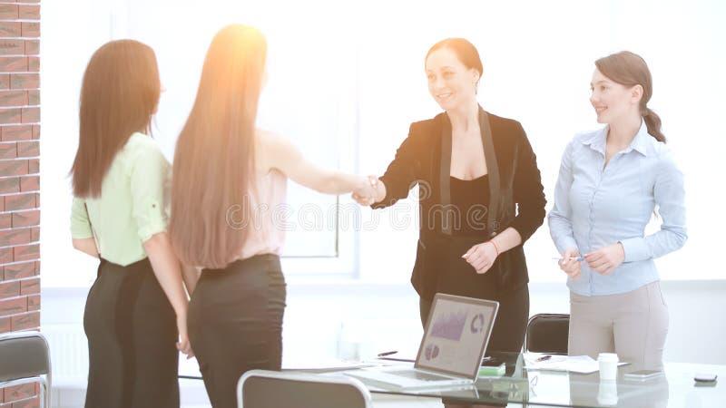 Más vieja mujer satisfecha y apretón de manos joven del encargado después de firmar el contrato en oficina fotografía de archivo