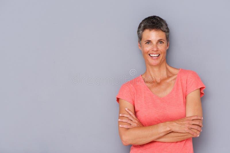Más vieja mujer sonriente contra la pared gris fotografía de archivo