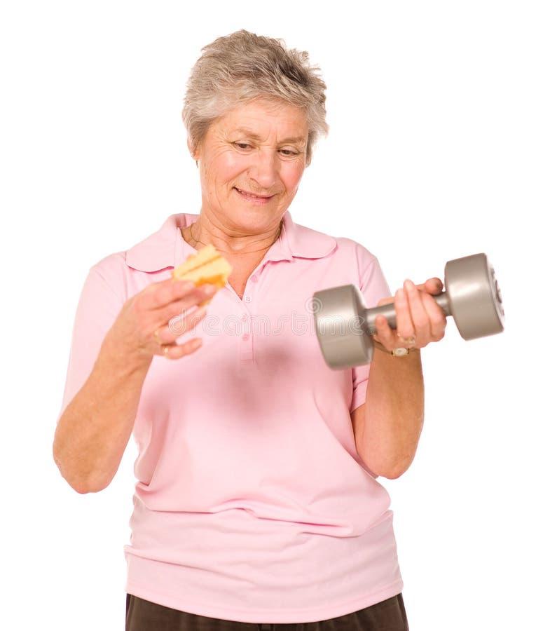 Más vieja señora madura que elige dieta o ejercicio imagen de archivo libre de regalías
