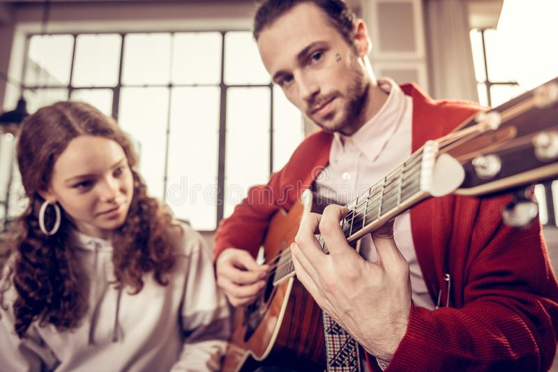 Más viejo hermano de ojos oscuros hermoso que toca la guitarra para la hermana imagen de archivo libre de regalías