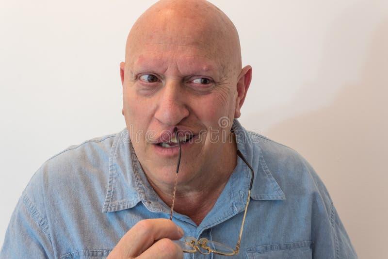 Más viejo hombre espeluznante que sostiene los vidrios con los ojos que miran al lado que sostiene los vidrios a los labios, calv fotos de archivo