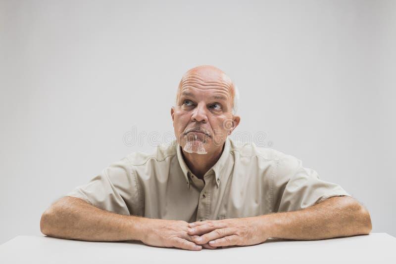 Más viejo hombre semicalvo pensativo que se sienta en una tabla imagenes de archivo