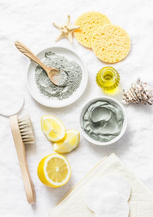 Máscara caseiro do facial da beleza Argila, limão, óleo, escova facial - ingredientes dos produtos de beleza no fundo claro foto de stock royalty free
