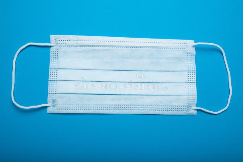Máscara cirúrgica do Orelha-laço no fundo azul, conceito fotos de stock royalty free