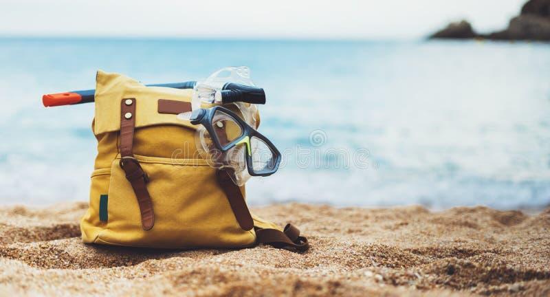 A máscara da trouxa e da natação do amarelo do turista do caminhante do moderno no horizonte azul do oceano do mar do fundo na ar imagem de stock