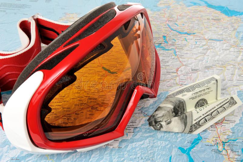 Máscara de esquí alpina con el aeroplano hecho del dinero en mapa fotografía de archivo