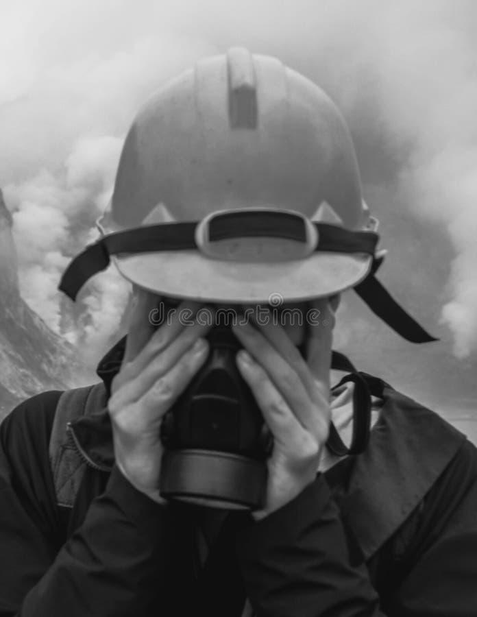 Máscara de gás do homem e capacete de segurança vestindo foto de stock royalty free