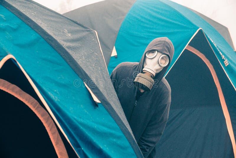 Máscara de gás dos turistas fora das barracas fotografia de stock