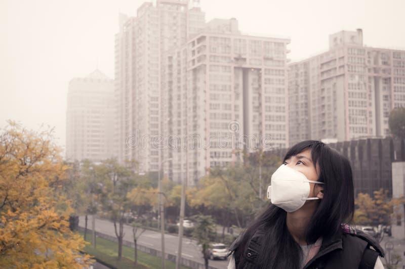 Máscara de la boca de la muchacha que lleva asiática contra la contaminación atmosférica de la neblina foto de archivo