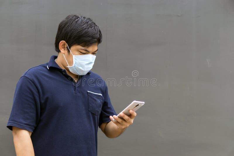 Máscara de la boca del hombre que lleva asiático contra la contaminación atmosférica imagenes de archivo