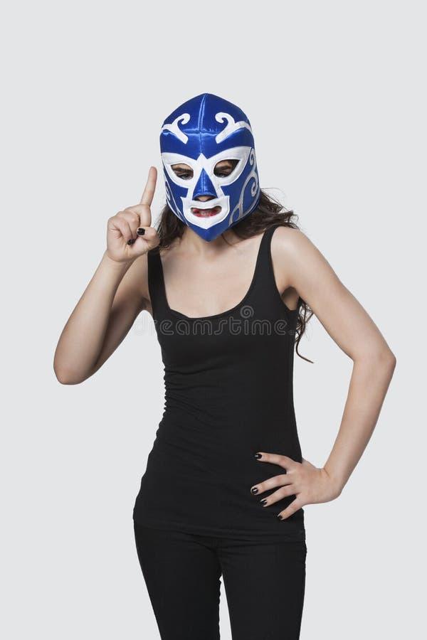 Máscara de lucha que lleva de la hembra joven como ella aumenta el dedo índice contra fondo gris foto de archivo libre de regalías