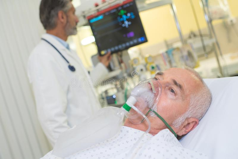 Máscara de oxigênio vestindo de exame do paciente do doutor foto de stock