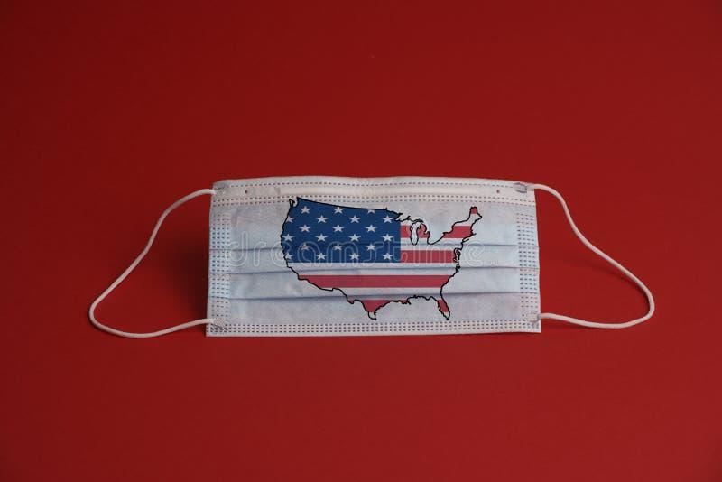 Máscara de proteção contra o coronavírus Máscara médica com bandeira americana combinada com mapa Fundo vermelho Proteção contra  foto de stock