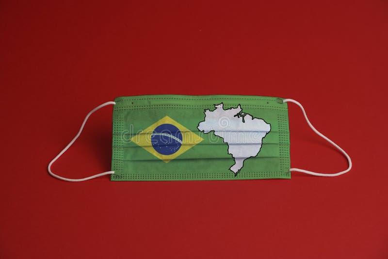 Máscara de proteção contra o coronavírus Máscara médica com bandeira e mapa do Brasil Fundo vermelho Proteção contra máscara de r foto de stock royalty free