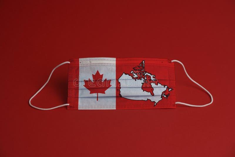 Máscara de proteção contra o coronavírus Máscara médica com bandeira e mapa do Canadá Fundo vermelho Proteção contra máscara de r fotografia de stock