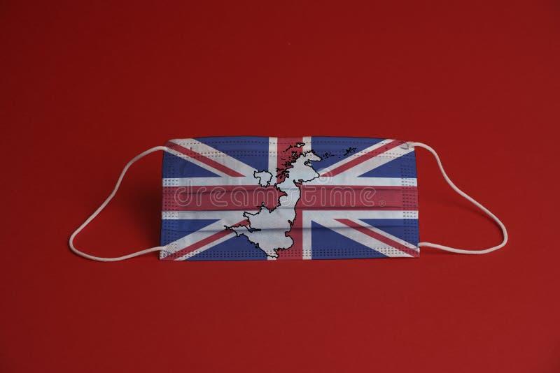 Máscara de proteção contra o coronavírus Máscara médica com bandeira e mapa do Reino Unido Fundo vermelho Proteção contra máscara foto de stock royalty free