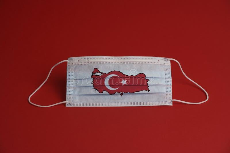 Máscara de proteção contra o coronavírus Máscara médica com bandeira e mapa turcos Fundo vermelho Proteção contra máscara de rost fotos de stock royalty free