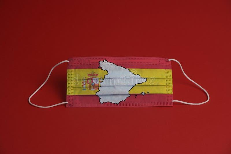 Máscara de proteção contra o coronavírus Máscara médica com bandeira espanhola junto com mapa Fundo vermelho Proteção contra másc foto de stock