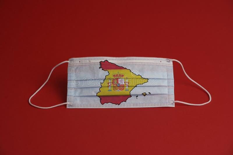 Máscara de proteção contra o coronavírus Máscara médica com bandeira espanhola junto com mapa Fundo vermelho Proteção contra másc imagem de stock