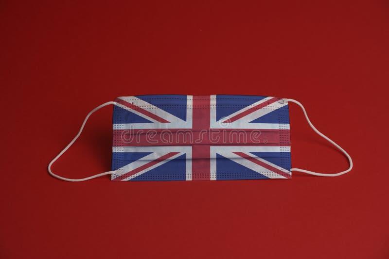 Máscara de proteção contra o coronavírus Máscara médica combinada com a bandeira do Reino Unido Fundo vermelho Proteção contra má fotografia de stock