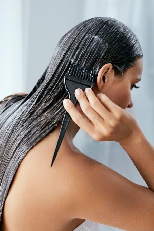 Máscara do cabelo Mulher que aplica o condicionador no cabelo longo com escova, tratamento dos cuidados capilares imagem de stock royalty free