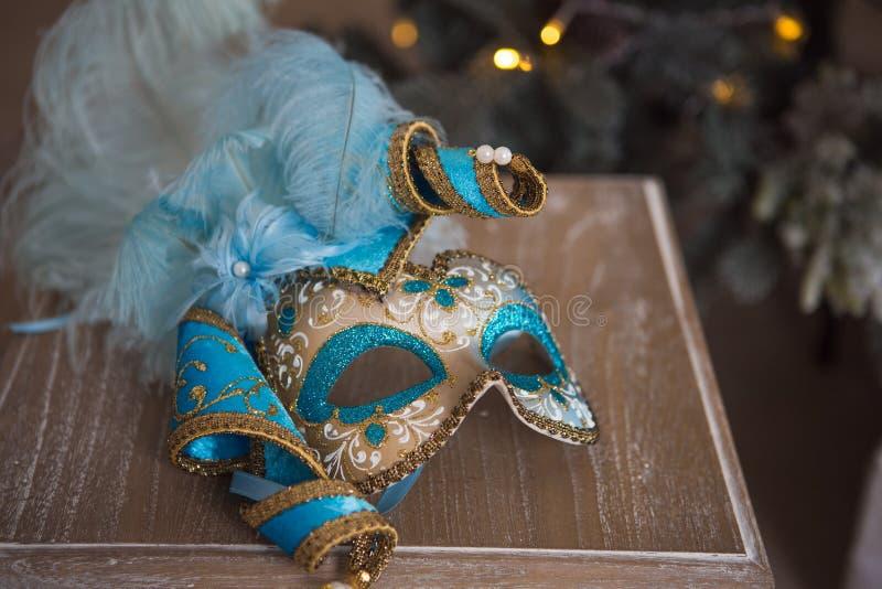 Máscara do carnaval do azul e do ouro que encontra-se em uma cadeira de madeira imagem de stock