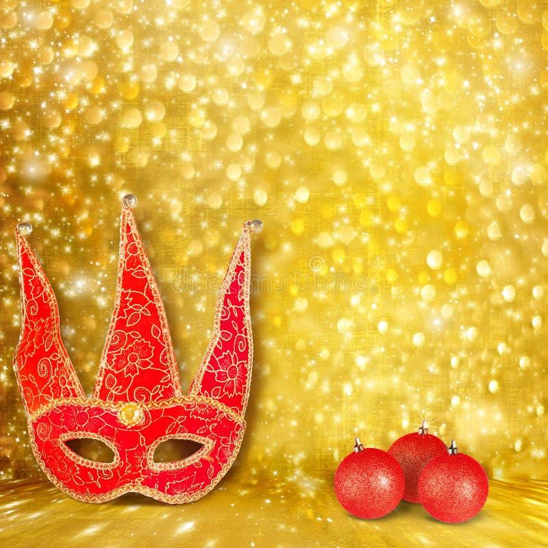 Máscara do carnaval e uma bola vermelha do Natal fotografia de stock