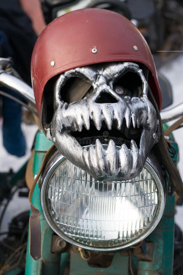Máscara do ferro sob a forma de um crânio em um capacete que encontra-se em um farol da motocicleta imagens de stock