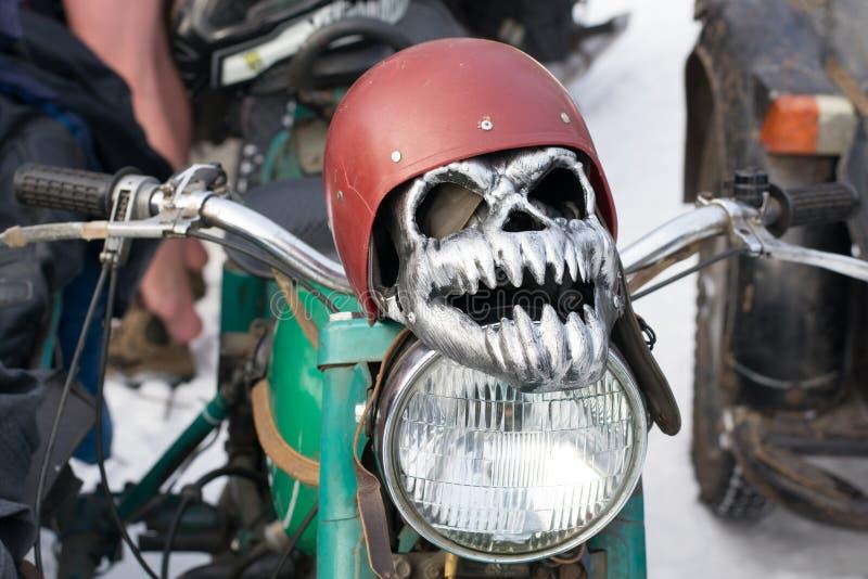 Máscara do ferro sob a forma de um crânio em um capacete que encontra-se em um farol da motocicleta imagens de stock royalty free