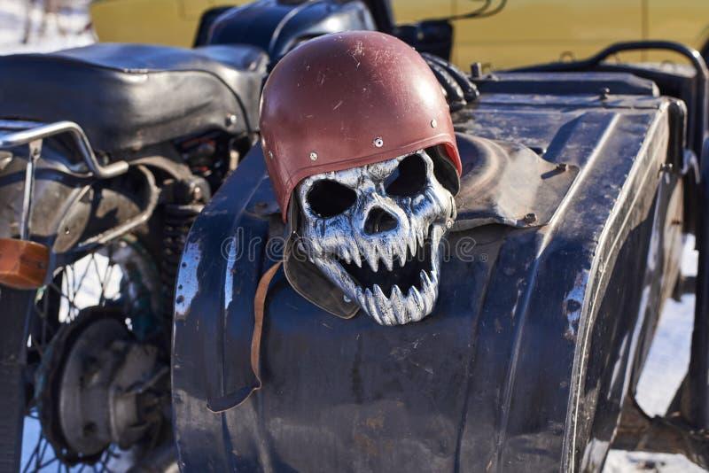 Máscara do ferro sob a forma de um crânio em um capacete que encontra-se em uma motocicleta imagem de stock