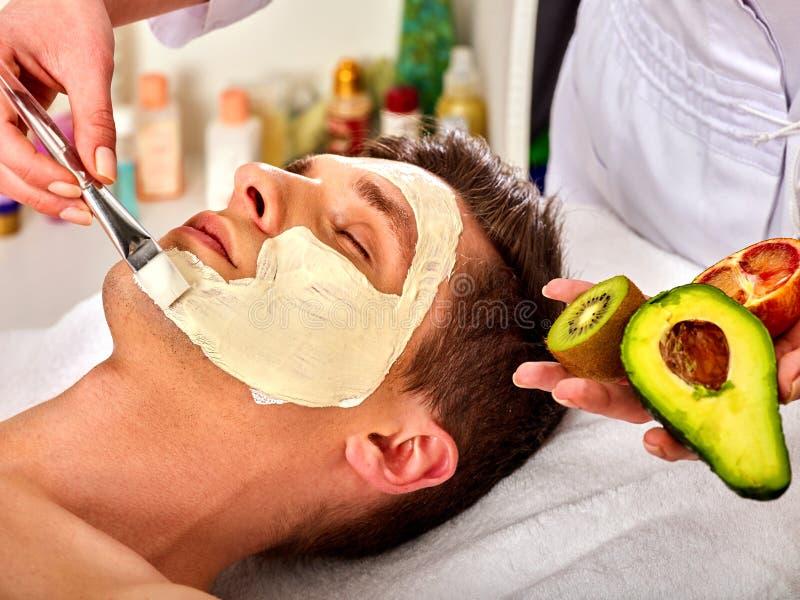 Máscara facial de las frutas frescas para el hombre El cosmetólogo aplica rebanadas fotos de archivo libres de regalías