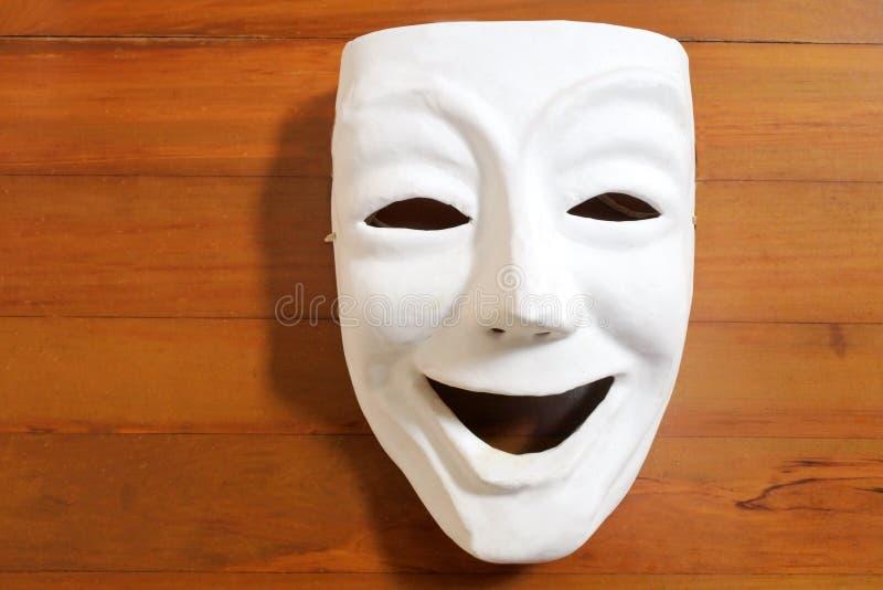Máscara feliz blanca de la expresión del rostro humano con encendido una tabla de madera imagen de archivo libre de regalías