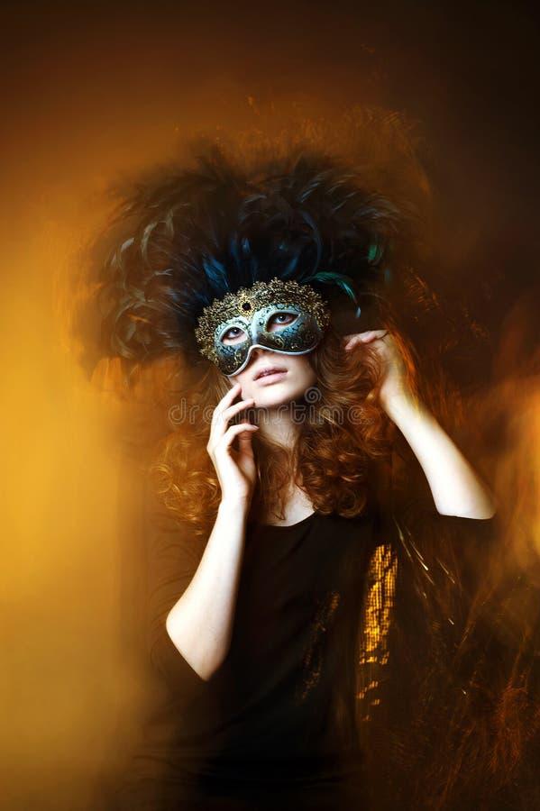 Máscara hermosa del carnaval de la mujer que lleva joven con las plumas imagen de archivo libre de regalías