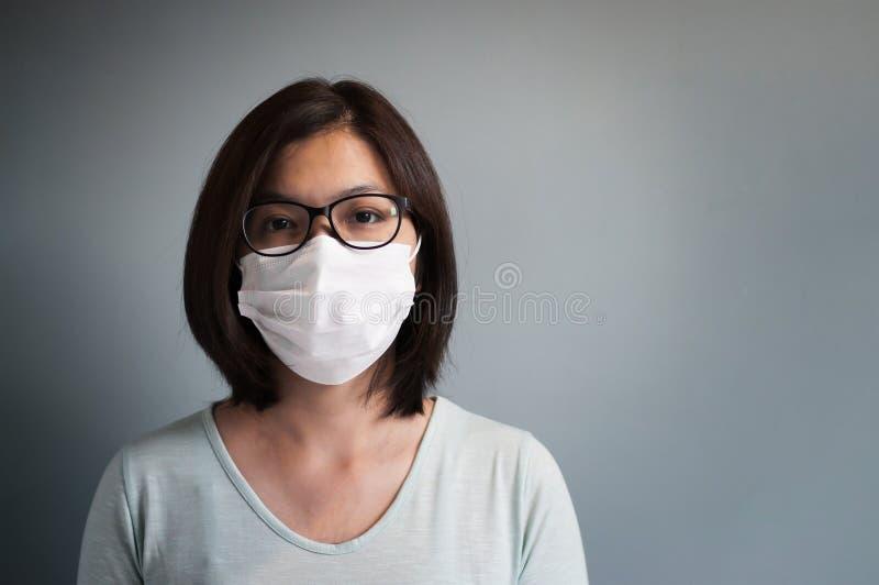Máscara médica asiática del desgaste de mujer de los vidrios imagen de archivo