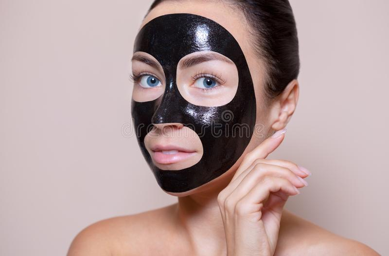 Máscara preta na cara de uma mulher bonita Tratamentos e cuidados com a pele dos termas no salão de beleza imagens de stock royalty free