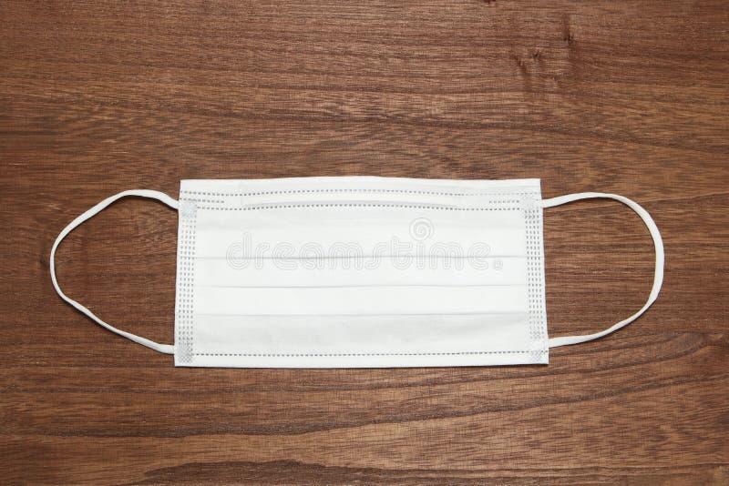 Máscara protetora descartável na madeira, máscara cirúrgica do Orelha-laço fotografia de stock royalty free