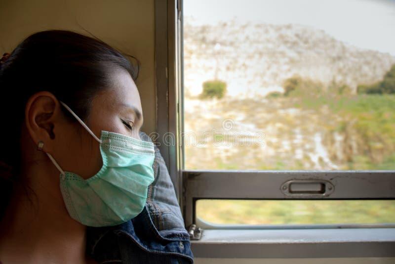 Máscara protetora vestindo da mulher asiática devido à poluição do ar no trem que senta-se perto da janela fotografia de stock royalty free