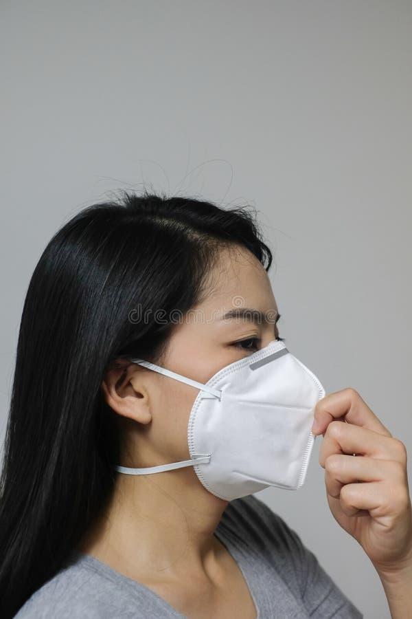 A máscara protetora vestindo da mulher de N95 devido à poluição do ar na cidade tem as partículas ou o PM 2 5 fotografia de stock