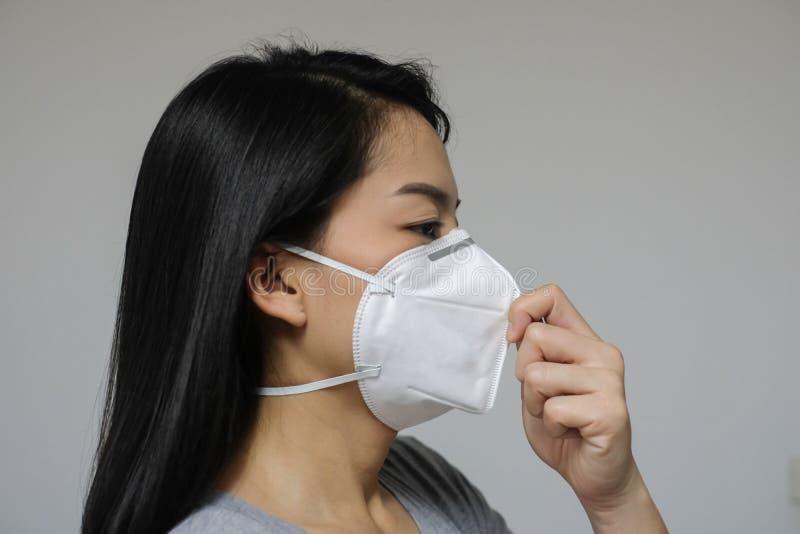 A máscara protetora vestindo da mulher de N95 devido à poluição do ar na cidade tem as partículas ou o PM 2 5 imagens de stock