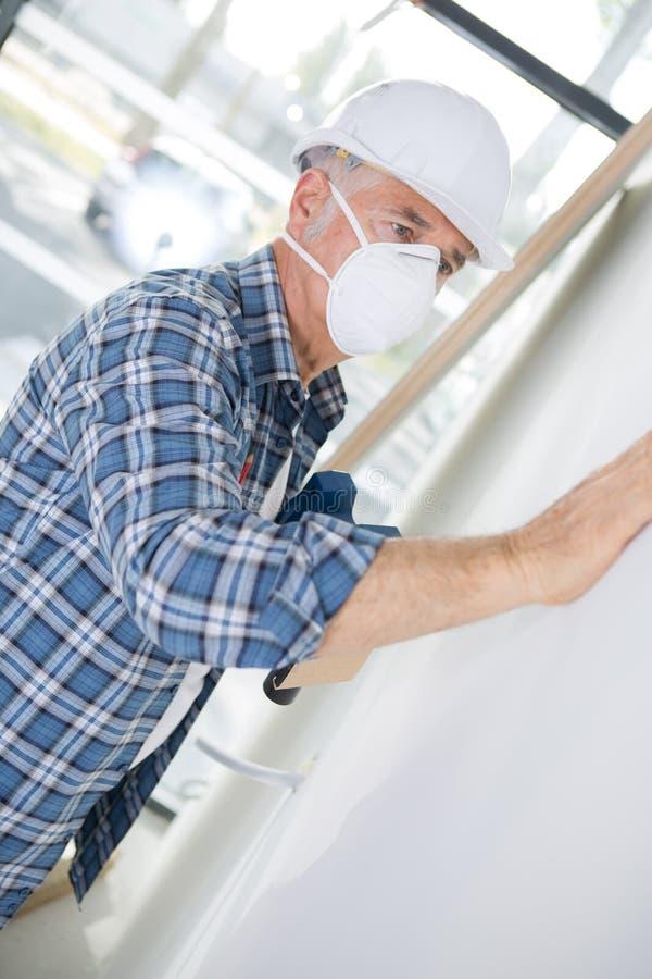 Máscara protetora vestindo do homem enquanto lixando a parede foto de stock royalty free