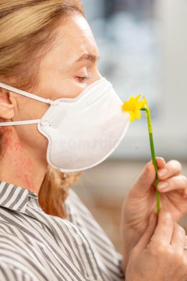 Máscara que lleva de la mujer mientras que teniendo alergia a las flores imagen de archivo