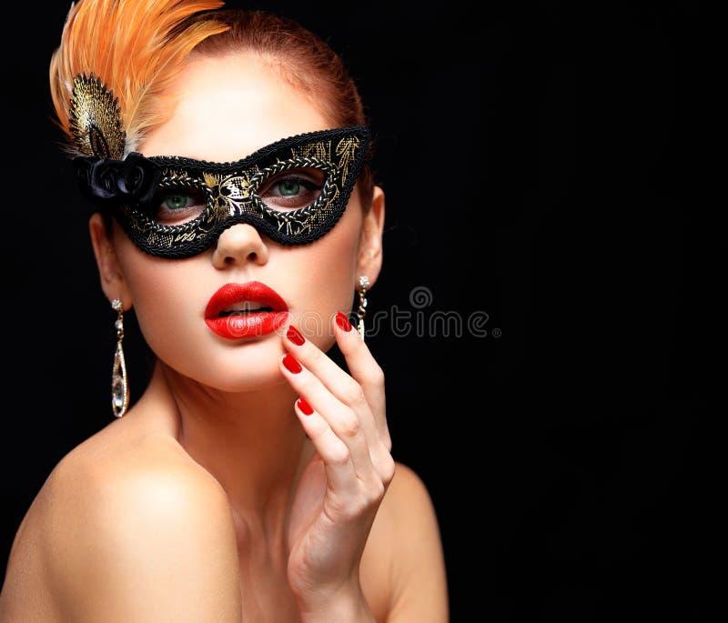 Máscara veneciana del carnaval de la mascarada de la mujer modelo de la belleza que lleva en el partido aislado en fondo negro La imagenes de archivo