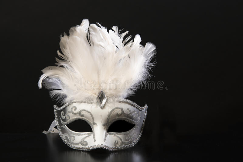 Máscara venetian branca e de prata do carnaval com penas em um fundo preto fotografia de stock
